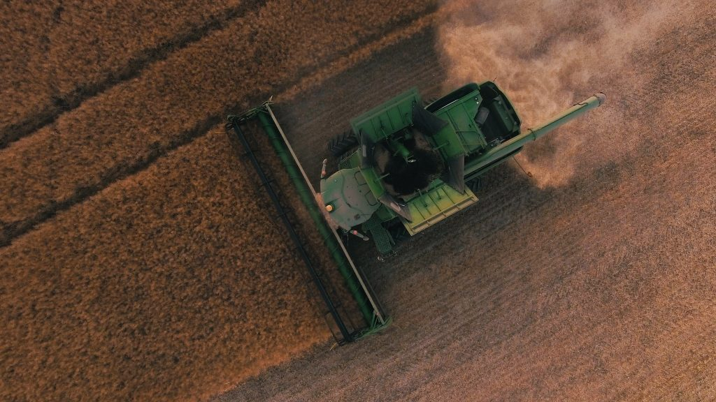 combine harvesting in farm field